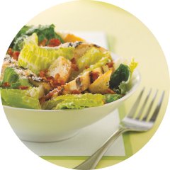 A caesar salad topped in a white bowl with a fork on the side