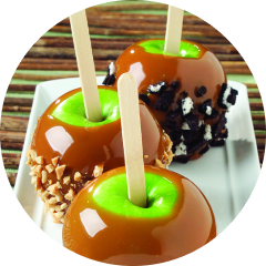 Three caramel apples on a white plate