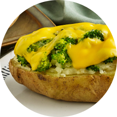 A baked potato topped with brocolli and cheese sauce