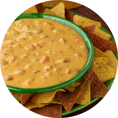 Dipping sauce in a green bowl on top of a stack of nacho chips