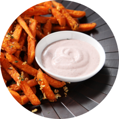 A white bowl of KRAFT marshmallow creme and caramel sauce surrounded by sweet potato fries