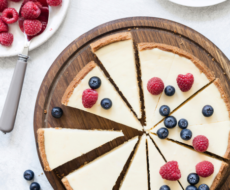 Top view of a sliced cheesecake with raspberries and blueberries on a wooden circle plate